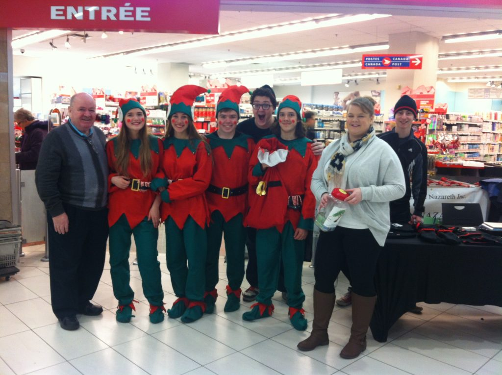 Volunteers gathered in a store dressed as elves